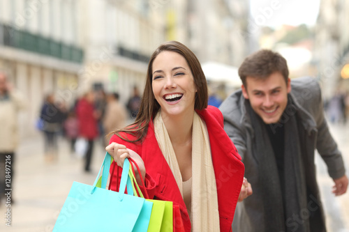 Couple of shoppers running with shopping bags