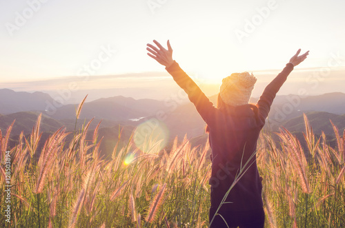 Leinwandbild Motiv Carefree Happy Woman Enjoying Nature on grass meadow on top of mountain cliff with sunrise. Beauty Girl Outdoor. Freedom concept. Len flare effect. Sunbeams. Enjoyment.