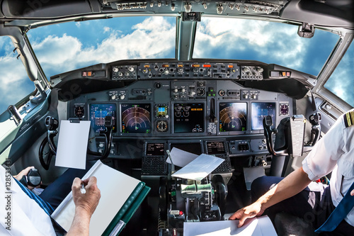Airplane cockpit flying in a cloudy blue sky at day. with pilots arms and blank white papers for copy space. - 128533431