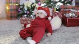 Baby boy in Santa costume sitting under the Christmas tree and falls.