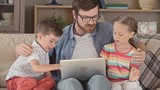 Beard young father  in eyeglasses sitting with his daughter and son on sofa and teaching them  to use laptop