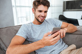 Cheerful young man lies on sofa and chatting