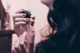 donna che spruzza il profumo sul collo - 128577839