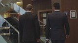 Rear view of two businessmen walking upstairs with briefcases in the hotel