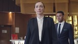Confident businesswoman walking through hotel lobby with two male colleagues following her