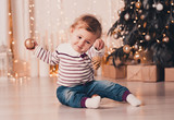 Smiling baby girl under 1 year old playing with Christmas ball over Christmas tree in room. Sitting on floor, wearing stylish knitted sweater. Celebration. Holiday season.