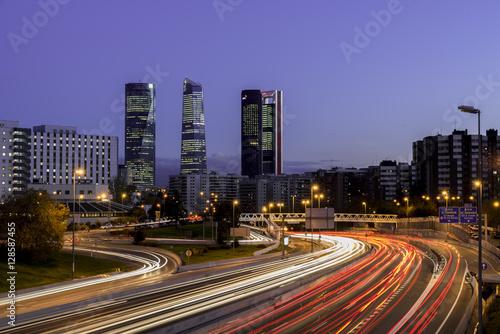 Foto op Canvas Madrid Atardecer de Madrid con los rascacielos y las luces de la carretera