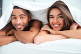 Happy young couple lying under the duvet in bed