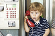 The emotions of a little boy talking on the phone. A conversation on the landline. Emotions. The voice of the red handsets