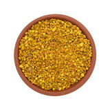 Bowl of bee pollen granules on a white background top view.