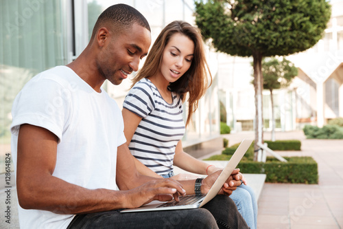 Poster Multiethnic couple using laptop together outdoors