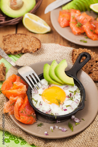 Poster Fried egg, avocado and smoked salmon in frying pan
