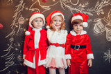 Children dressed as Santa Claus standing on dark background with Christmas pattern. New Year.