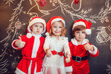 Children dressed as Santa Claus standing and show thumb on dark background with Christmas pattern. New Year.
