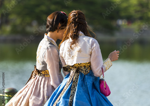 Two Korean girl dressed in old traditional dress talking at the lake in a park Poster