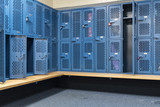 Blue metal cage lockers in a locker room with some doors open and some closed with a wooden bench