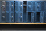 Blue metal cage lockers in a locker room with some doors open and some closed with a wooden bench - 128688492