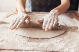 Hands baking bread or pizza dough with rolling pin on wooden table