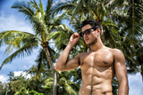 Handsome shirtless fit athletic young man lifting his sunglasses, shot from below
