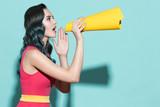 Young beautiful girl speaks in a yellow paper loudspeaker.