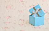 Christmas background - Blue small gift boxes on hand with decorations small gift boxes on wooden board background.
