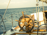Steering wheel on the old sailboat. Sea voyage of the sailing vessel. Travel at sail boat with a wooden helm in front. Ship wheel on the old yacht - nautical equipment closeup.