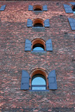 Several arched windows with shutters, fastened to a brick facade of a former industrial building in Dumbo New York