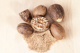 Nutmeg , whole and half on wooden plank, close up - 128744887