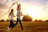 familie mit tochter rennt und lässt drachen steigen - 128768481