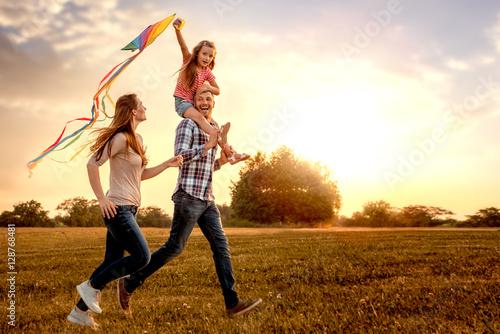 Fototapeta familie mit tochter rennt und lässt drachen steigen