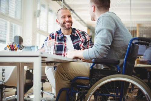 Handicap businessman sitting with colleague in office
