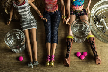 Dolls partying with shots of vodka, pink pills and stubbed cigarettes - mepaphor of recreational drugs abuse among young people