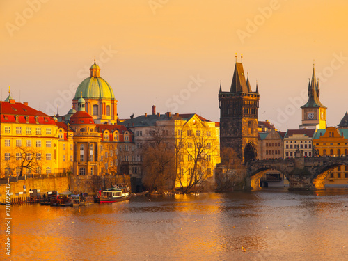 Poster Prague Evening. Towers of Old Town and Charles Bridge over Vltava River illuminated by orange sunset. UNESCO World Heritage Site. Prague, capital city of Czech Republic, Europe