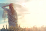 dreamy woman looks at infinity as the sun rises - 128833282