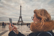 Using cellphone with Paris background from Trocadero.