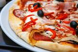 Pizza z czerwoną świeżą papryką i czarnymi oliwkami na bielu talerzu