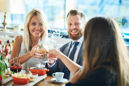 business people meeting in modern restaurant, colleagues having dinner and take drink after work - 128856484