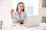Businesswoman holding glasses sitting and using laptop