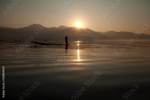 Poster Intha fisherman fishing at sunset in his typical canoe with fish