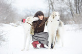girl with two greyhounds in the winter, falling snow