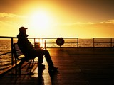 Tourist sit on wharf bench and enjoy misty sunny morning at sea. Smooth water