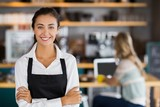 Portrait of smiling waitress standing with arms crossed - 128906601