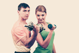 Couple exercising with dumbbells lifting weights