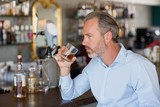 Serious man drinking whiskey at bar counter