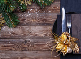 Christmas table place setting with black napkin, plate, fork and knife, decorated gold flower and christmas pine branches.
