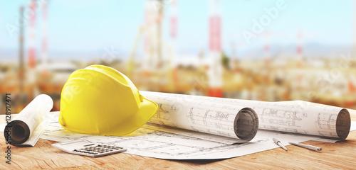 Żółty kask pracownika z projektami na budowie