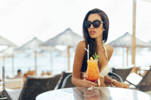 Poster Beautiful girl drinking cocktail on beach