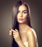 Beauty brunette model girl touching brown long healthy hair