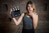 Young blonde actress amazed with movie clapper