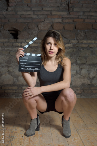 Young blonde actress crouched with movie clapper Poster
